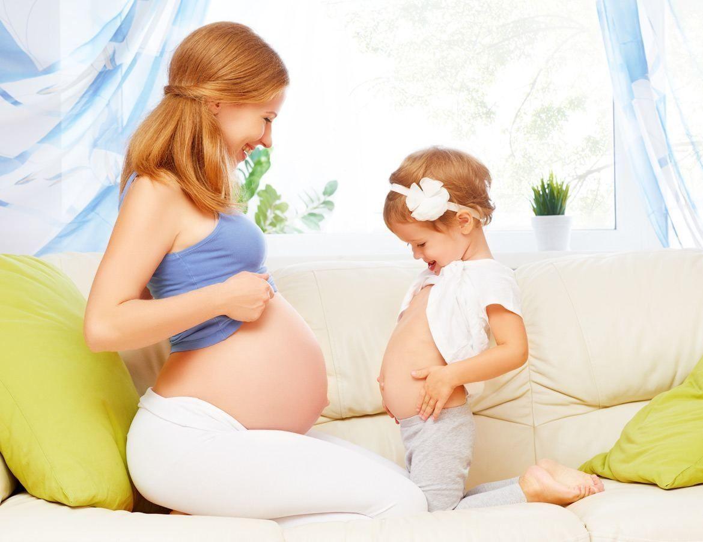 Беременная меряется животом с дочкой