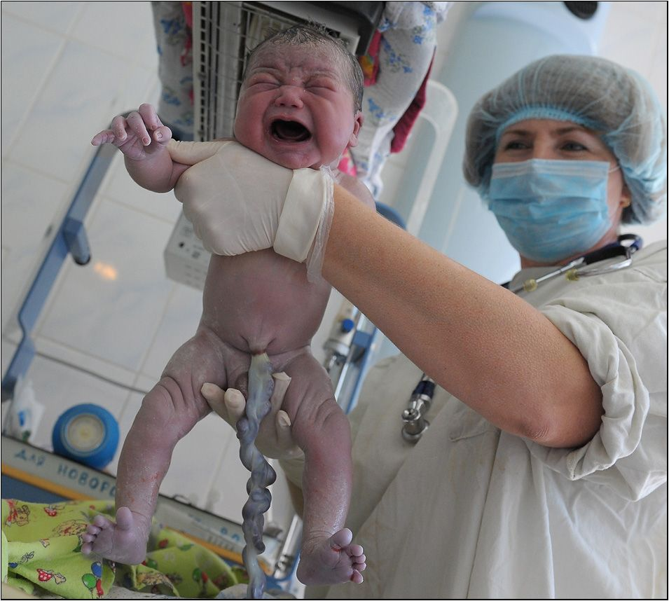 рожденный малыш с перевязанной пуповиной