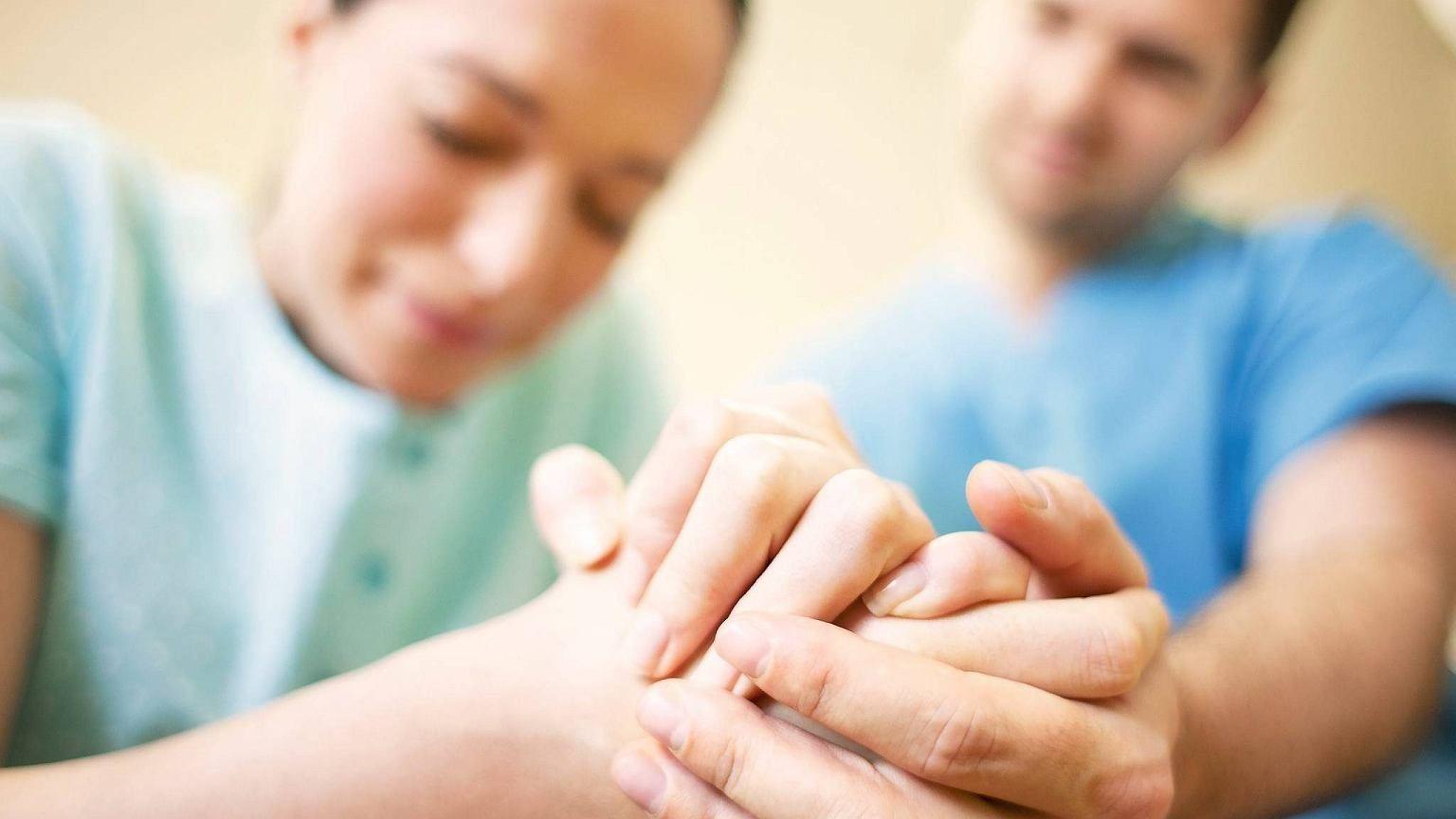 женщина перед родами держит врача за руку